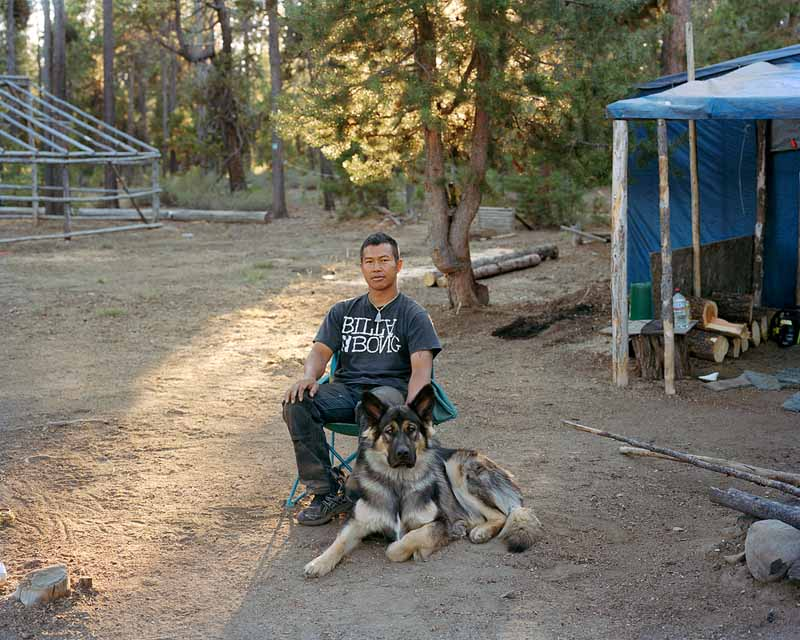 Eirik Johnson, Somphone with his dog Whiskey outside their shack in the Crescent Lake mushroom camp, Oregon, 2011