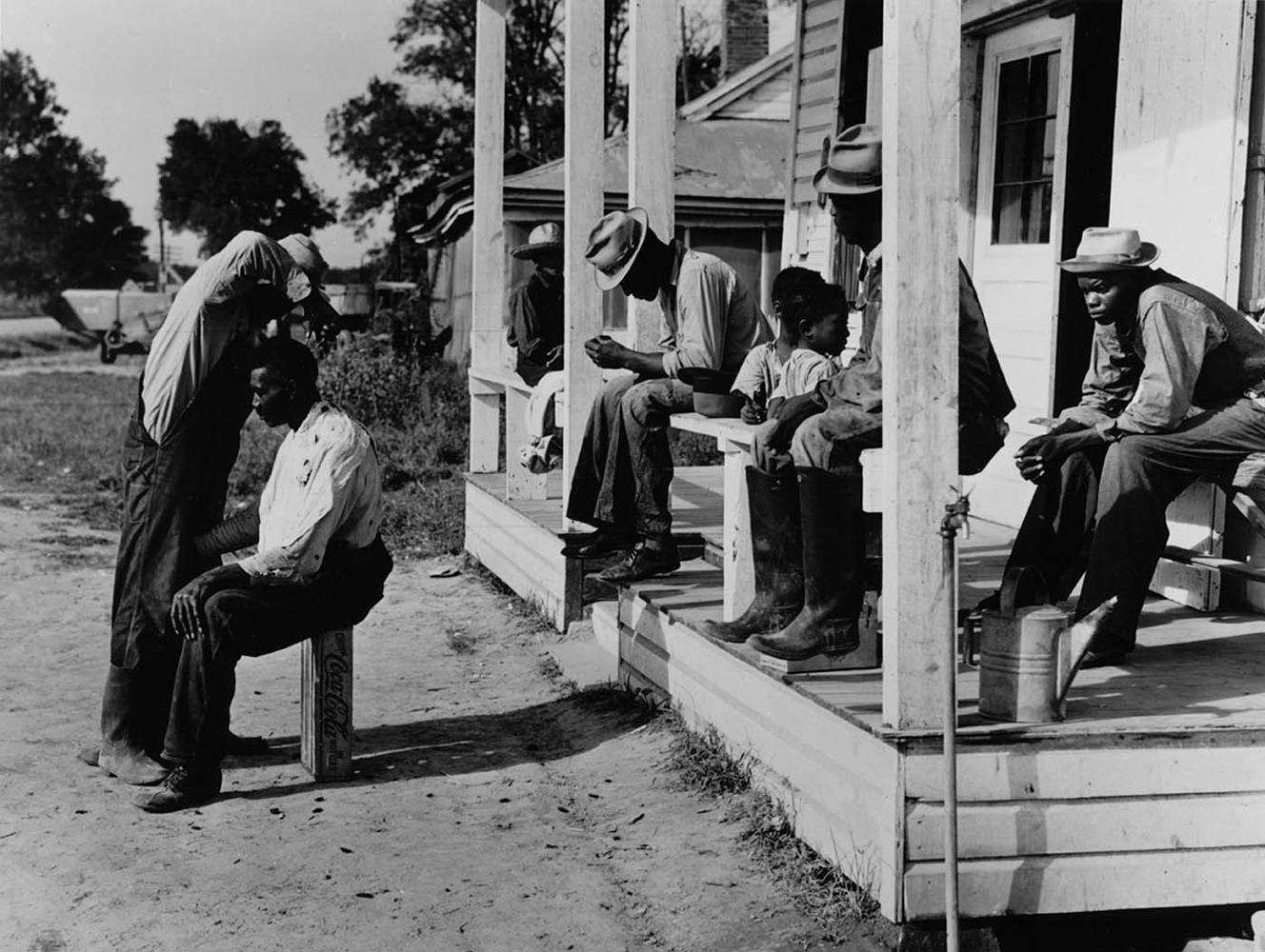 Marion Post Wolcott, Haircutting in front of general store, Marcella Plantation, Mileston, Mississippi, 1939 gelatin silver print, 11 x 14 inches, signed by artist, $3000.
