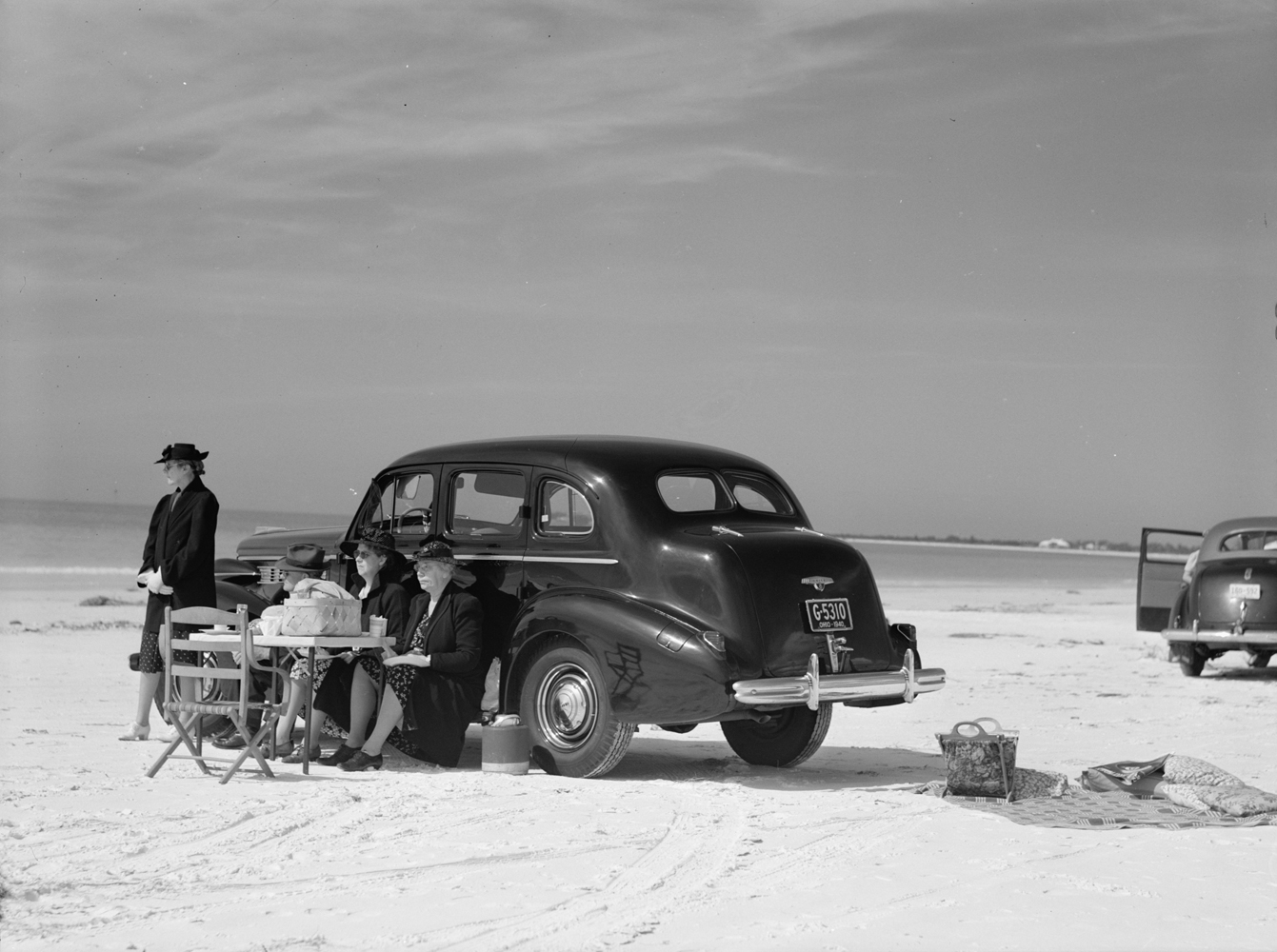 Marion Post Wolcott, Winter Visitors Picnicking on Running Board of Car on Beach, Sarasota, FL, 1941, gelatin silver print, 11 x 14 inches