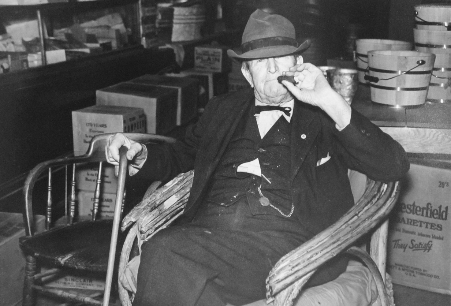 """Marion Post Wolcott, Mr. Whitely in his general store. He also owns a bank, cotton exchange, and real estate. He was the first man to settle in town; he cut down trees and pulled out stumps for """"main"""" street. Wendell, North Carolina, 1940, gelatin silver print, signed, 11 x 14 inches"""